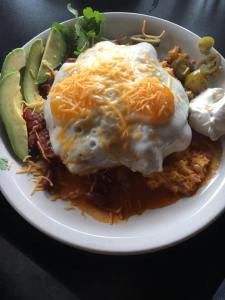 The Dish Huevos: Grilled polenta topped with our delicious house made chili and pimento cheese, two farm fresh eggs cooked to order and served with sliced avocado, a side of sour cream and jalapenos. It's become a favorite of locals! $11.95
